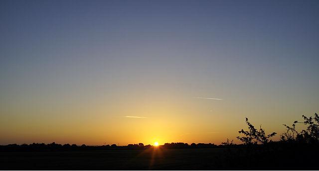 lieber so! Sonnenaufgang über Land, wolkenloser Himmel