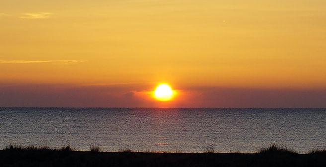 die Sonne steigt aus dem Dunst über der Kimm