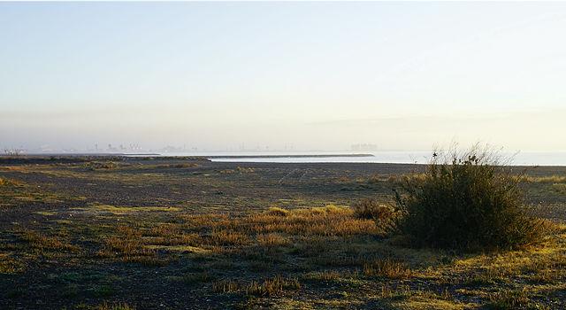 Strand im Morgenlicht, dahinter der Hafen von Sagunt