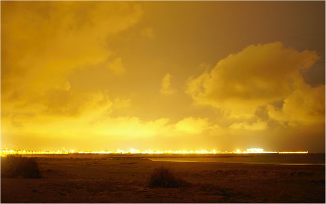 niedrig hängende Wolken, nachts von unten beleuchtet vom Hafen von Sagunt