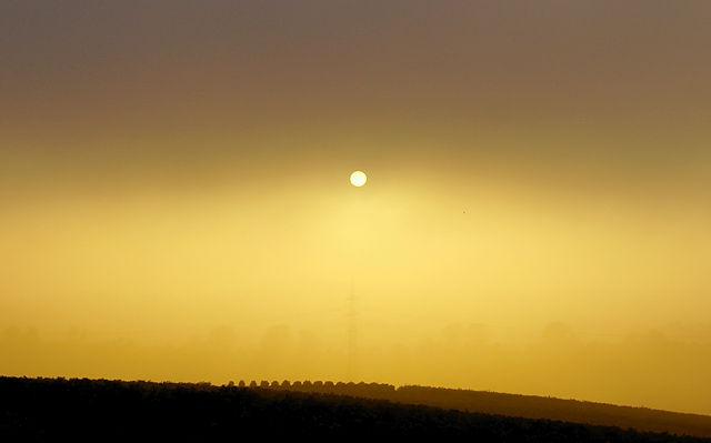 aus dem dichten Nebel oben sinkt die Sonne in den dünnen Nebel unten