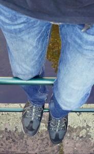 ab jetzt klammert sich der Gutmann mit den Beinen über das Geländer am Bach, mit leicht erhöhtem Blick auf den Umzug
